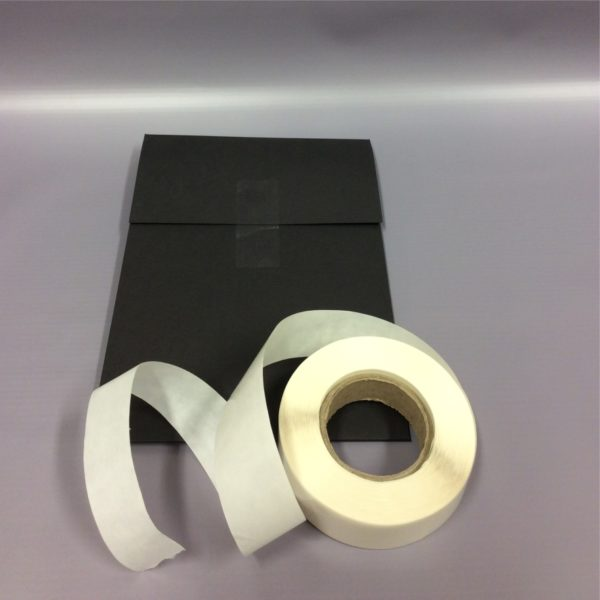 Clear 65x25mm Rectangle Sticker - Clear Sticker Visible on Black Card With Roll Partially Unraveled On Top