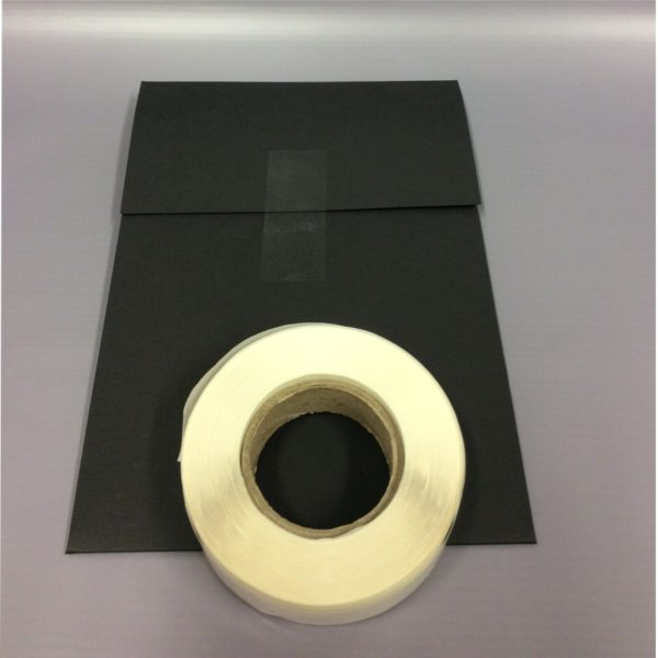 Clear 65x25mm Rectangle Sticker - Clear Sticker Visible on Black Card With Roll Sat On Top